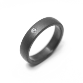 White 5 mm, svagt kupad med 0,04 ct briljant. Oxidized svart yta.